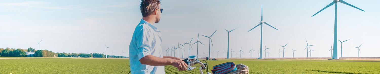 hombre mirando molinos de viento, menores emisiones de carbono, huella de carbono