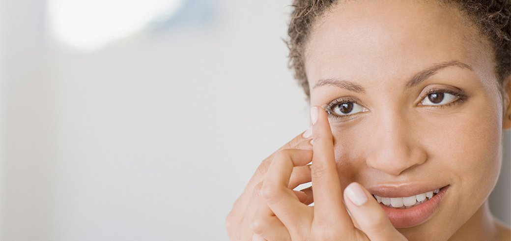 A woman with a contact lens on her finger about to put it in her eye